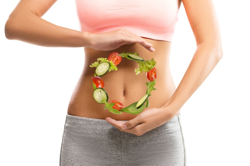 Fit, young woman holding a circle made out of vegetables over her abdomen