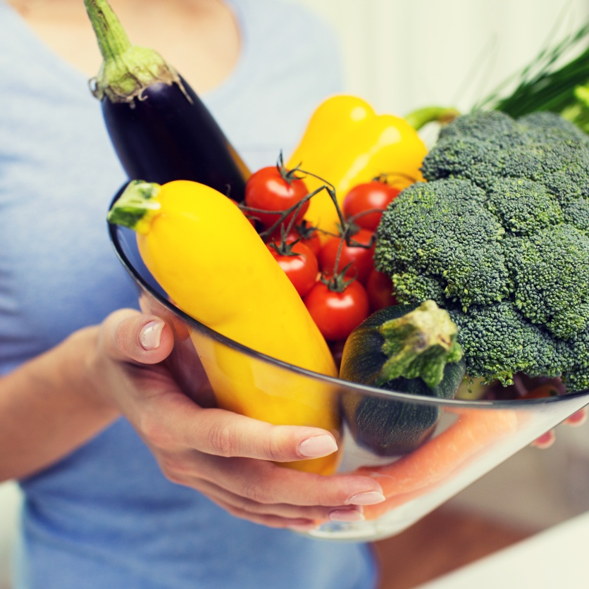 close up of woman holding vegetables in bowl